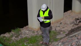 Ingenieur die documentatie controleren dichtbij brugbouw stock videobeelden