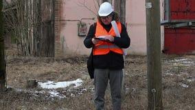 Ingenieur die documentatie controleren dichtbij powerline stock videobeelden