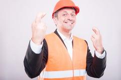 Ingenieur die dragend bouwvakker die vingers gekruist gebaar maken glimlachen Royalty-vrije Stock Fotografie