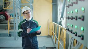 Ingenieur die een document in industriële fabriek ondertekenen stock footage