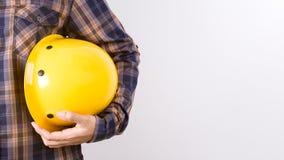 Ingenieur die een helm op witte achtergrond houden Stock Foto