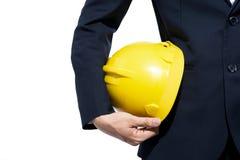 Ingenieur die gele helm voor arbeidersveiligheid houden op witte bac Stock Afbeeldingen