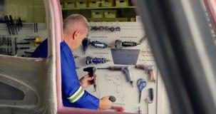 Ingenieur die hulpmiddelen controleren bij ruimtevaarthangaar 4k stock video