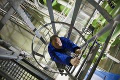 Ingenieur die in installatie beklimt Stock Foto