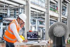 Ingenieur die laptop computer in thermische elektrische centralefabriek met behulp van royalty-vrije stock afbeelding