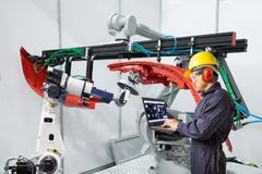 Ingenieur die laptop van de de robotgreep van het computeronderhoud het automobielwerkstuk, Slim fabrieksconcept gebruiken stock foto