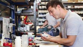 Ingenieur die mannelijke leerling in fabriek helpen om component te meten die micrometer gebruiken stock video