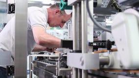 Ingenieur die met digitale tablet geautomatiseerde machine in fabriek controleren stock videobeelden