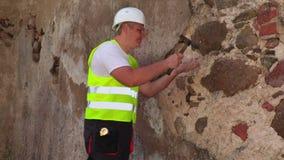 Ingenieur die met hamer pleister van oude muur controleren stock video
