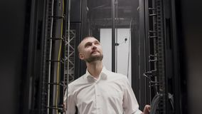 IT ingenieur die met laptop vóór open serverrek werken in ruimte stock footage