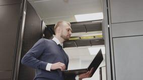 IT ingenieur die met serverrek en het systeem van het steundatacentrum werken stock video