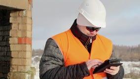 Ingenieur die met tabletpc dichtbij de onvolledige bouw werken stock footage