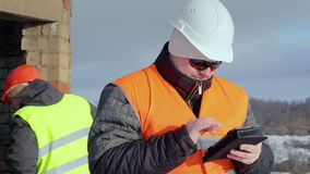 Ingenieur die met tabletpc dichtbij de onvolledige bouw werken stock videobeelden