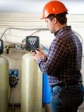 Ingenieur die meterlezingen van industriële pompen nemen bij fabriek stock foto