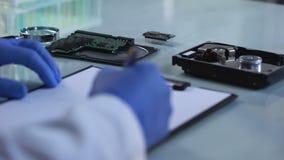 Ingenieur die microschakeling controleren en rapport, de reparatie van de computerraad, spaander vullen stock footage