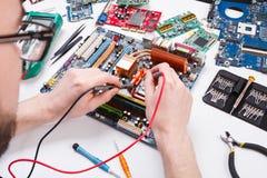 Ingenieur die motherboard met multimeter controleren royalty-vrije stock foto's