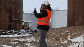 Ingenieur die op smartphone in de fabriek spreken dichtbij aan de olietanks in de winter stock footage