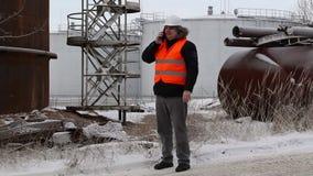 Ingenieur die op smartphone spreken dichtbij aan de olietanks stock videobeelden