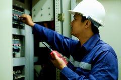 Ingenieur die schakelaar in het elektrokabinet aanzetten bij controlekamer stock afbeeldingen