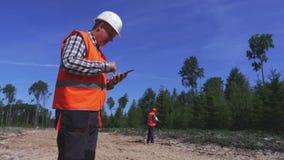 Ingenieur die smartphone op de nieuwe weg gebruiken stock videobeelden