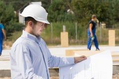 Ingenieur die specificaties controleren op een plan Stock Foto
