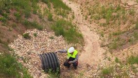 Ingenieur die stroompijp in diepe sloot controleren stock footage