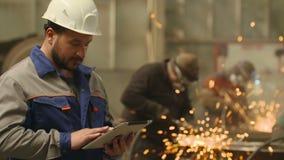 Ingenieur die Tabletpc binnen in zware industriefabriek met behulp van Malende vonkenachtergrond