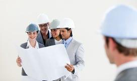 Ingenieur die terug zijn glimlachende collega's bekijkt Stock Foto's