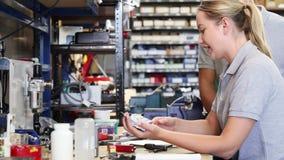 Ingenieur die vrouwelijke leerling in fabriek helpen om component te meten die micrometer gebruiken stock videobeelden