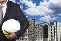 Ingenieur die witte helm voor arbeidersveiligheid houden Stock Afbeeldingen