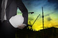 Ingenieur die witte helm voor arbeidersveiligheid houden Royalty-vrije Stock Afbeeldingen
