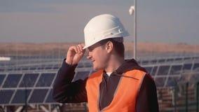 Ingenieur in einer orange Westenstellung mitten in dem Feld am Unternehmen setzt an seinen Kopf der weiße Sturzhelm und stock video footage