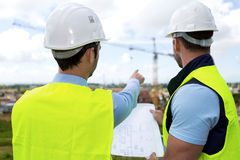 Ingenieur en arbeiders het letten op blauwdruk op bouwwerf Royalty-vrije Stock Foto's