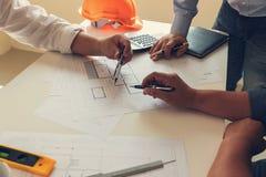 Ingenieur en Architectenconcept, het bureauteam die van IngenieursArchitects met blauwdrukken werken stock afbeeldingen