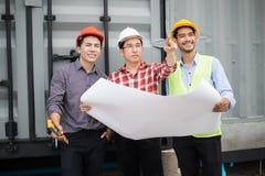 Ingenieur en bouwteam die veiligheidshelm en blauwdruk op hand dragen zij controleren vooruitgang van bouwwerf royalty-vrije stock foto