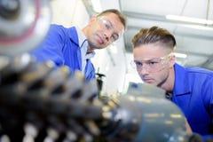 Ingenieur en leerling die materiaal bekijken stock foto