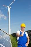 Ingenieur am Energiepark mit Sonnenkollektoren und Windkraftanlage Stockbild
