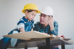 Ingenieur Father, der seinen Sohn unterrichtet, das Bauplanpapier zu lesen lizenzfreie stockfotografie