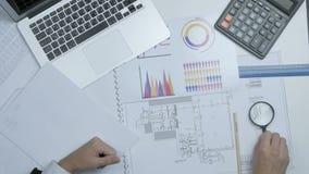 Ingenieur, financier gebruiken meer magnifier, loupe werkend met blauwdrukken die berekeningen maken stock video