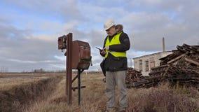 Ingenieur gebruikend tablet en controlerend grondgebied stock footage