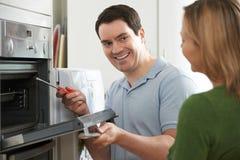 Ingenieur Giving Woman Advice op Keukenreparatie stock afbeelding