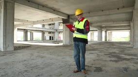 Ingenieur im gelben Sturzhelm bleibt auf Baustelle stock footage