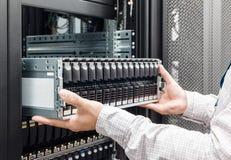 IT-Ingenieur installiert Einschließung mit Festplattenlaufwerk in das Speichersystem Stockfoto