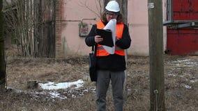 Ingenieur met documentatie dichtbij powerline stock footage