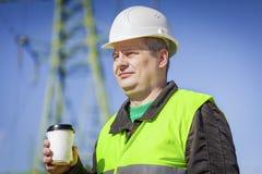 Ingenieur met koffie dichtbij hoogspanning towe Stock Afbeeldingen