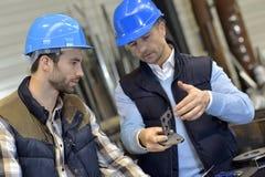 Ingenieur met mechanische arbeider die op kwaliteitsproducten controleren stock afbeelding