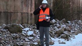 Ingenieur met smartphone en documentatie stock footage