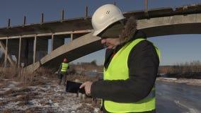 Ingenieur met tabletpc dichtbij de brug stock videobeelden