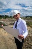 Ingenieur mit Plänen auf Standort Lizenzfreie Stockbilder