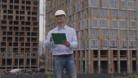 Ingenieur mit weißem Sturzhelm und Klemmbrett stock video